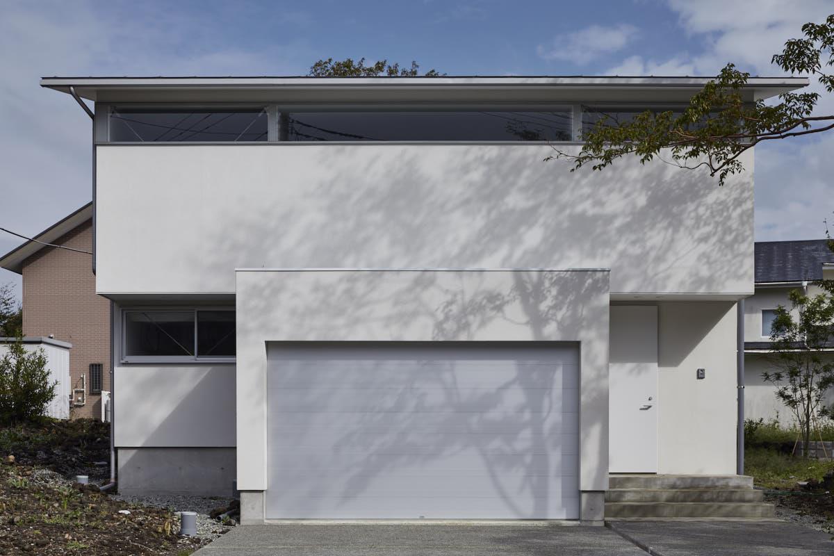 木漏れ日の影が外観のアクセント、建物の主役となるガレージ